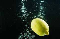 Lemon in water on a black background. With bubbles Royalty Free Stock Photo