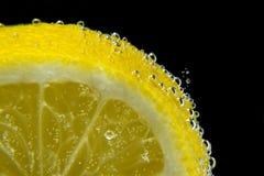 Lemon water bubbles black background close-up macro Royalty Free Stock Photography