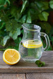 Lemon water. Cold lemon water with mint in a glass jug Stock Photo