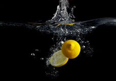 Lemon in water. Lemon falling into the water with a splash of water and air bubbles. On a black background. Wash fruits Stock Photography