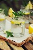 Lemon water in glass jars. Royalty Free Stock Image