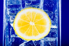 Lemon, water and ice Stock Photo
