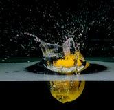 Lemon into water, isolated on black Stock Image