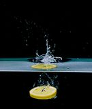 Lemon into water, isolated on black Royalty Free Stock Photo