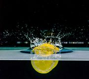 Lemon into water, isolated on black Stock Photos