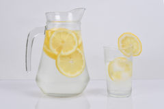 Lemon water in a jug. And a cup with a slice of lemon Stock Photos
