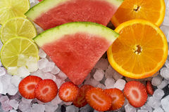 Lemon, watermelon, orange and strawberries. High angle shot of some slices of lemon, watermelon, orange and strawberries on a pile of ice Royalty Free Stock Images