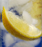 Lemon Wedge in Glass Mineral Water with Ice. Lemon Wedge in Glass of Cold Mineral Water with Ice. Closeup royalty free stock images