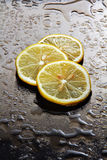 Lemon on a wet glass. Royalty Free Stock Image