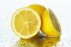Lemon on wet surface Stock Photos