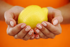 Lemon in woman hands Royalty Free Stock Photography