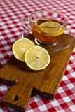 Lemon on a wood board and cup of tea Stock Photos