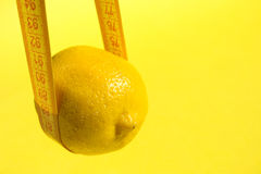Lemon on yellow background and measure tape, copy Royalty Free Stock Photo