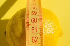 Lemon on yellow background and measure tape Royalty Free Stock Photo