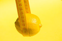 Lemon on yellow background and measure tape Royalty Free Stock Photos
