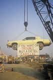 A lemon-yellow Cadillac, which has apparently lived up to its color, hangs from a crane near a service station. A sign warns futur Royalty Free Stock Photos