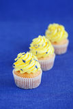 Lemon yellow cupcakes. Lemon cupcakes with lemon buttercream and dried cornflower petals, selective focus Royalty Free Stock Photos