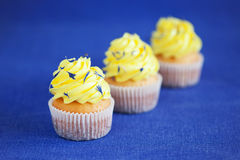 Lemon yellow cupcakes. Lemon cupcakes with lemon buttercream and dried cornflower petals, selective focus stock photos