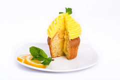 Lemon yellow cut cupcake with mint on a white background. Stock Photo