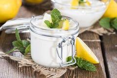 Lemon Yoghurt. Portion of fresh homemade Lemon Yoghurt on wooden background (with some fresh Mint royalty free stock image