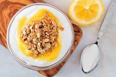 Lemon yogurt with granola, overhead scene on white marble Royalty Free Stock Photography