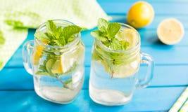 Lemonad con las rebanadas del limón y la menta en un tarro asaltan foto de archivo