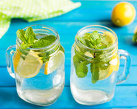 Lemonad con las rebanadas del limón y la menta en un tarro asaltan con la paja imagenes de archivo