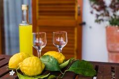 Lemonad eller limoncello i en glasflaska, exponeringsglas, citroner med sidor på en portiontabell på terrassen royaltyfri fotografi