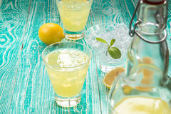 Lemonad eller limoncello i okproppflaska royaltyfri foto