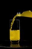 Lemonad hälls in i exponeringsglaset, på en svart bakgrund Arkivfoton