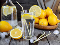 Lemonad i ett genomskinligt exponeringsglas och citroner på en trätabell Arkivbild