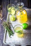 Lemonad i flaska och två exponeringsglas på tappning belägger med metall magasinet spelrum med lampa royaltyfri fotografi