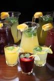 Lemonad i tillbringaren och citronerna med mintkaramellen på tabellen inomhus Royaltyfri Bild