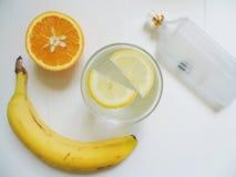 lemonad med citronen, apelsinen, bananen och eau de toilette på vit bakgrund royaltyfri fotografi