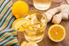 Lemonad med citronen och ingefäran i ett genomskinligt exponeringsglas på en trätabell Arkivfoto