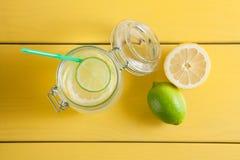 Lemonad med is, citronen och limefrukt i en krus på gula trälodisar royaltyfri fotografi