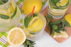 lemonad med citronen och mintkaramellen i en glass tillbringare och ett exponeringsglas bredvid den nya citronen på en vit träbak arkivbild