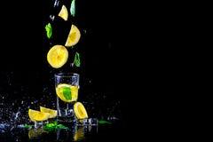 Lemonad med den flygcitronen och mintkaramellen som isoleras på en svart bakgrund, fritt utrymme arkivfoto
