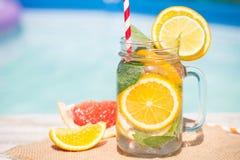 Lemonad med den nya apelsinen och grapefrukten i den blåa pölen tropisk coctail Idyllisk sommarferie Royaltyfri Bild
