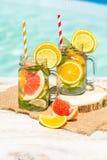 Lemonad med den nya apelsinen och grapefrukten i den blåa pölen tropisk coctail Idyllisk sommarferie Arkivfoto