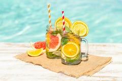 Lemonad med den nya apelsinen och grapefrukten i den blåa pölen tropisk coctail Idyllisk sommarferie Royaltyfria Bilder