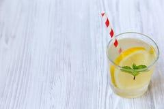 Lemonaddrink i ett exponeringsglas med den nya citronen och mintkaramellen över vit träbakgrund, sidosikt arkivfoton