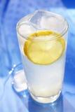 Lemonade. Lemon slice covered with ice water stock photo