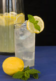 Lemonade. A tall glass of ice cold lemonade garnished with lemon and fresh mint, and a pitcher of lemonade in the background royalty free stock photography