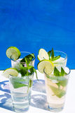Lemonade against blue background, with mint and lime. Limo Royalty Free Stock Images