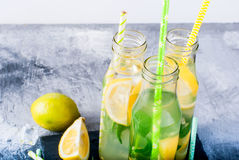 Lemonade in bottles with ice and mint Stock Photo
