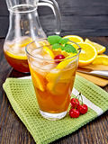 Lemonade with cherries in glassful and jug on board Stock Photo