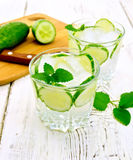Lemonade with cucumber and mint in two glassful on light board Stock Photo