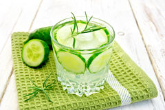 Lemonade with cucumber and rosemary in glassful on napkin. Lemonade with a cucumber and rosemary in a glass on a green napkin on the background light wooden Stock Photos