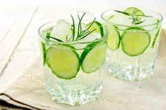 Lemonade with cucumber and rosemary in two glassful on napkin. Lemonade with a cucumber and rosemary in two glassful on beige napkin against the background light Royalty Free Stock Images